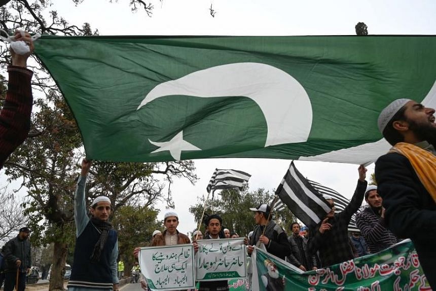 Pakistani activists from several religious parties holding up a Pakistani flag as they shouted anti-Indian slogans during a protest in Islamabad on March 1, 2019.