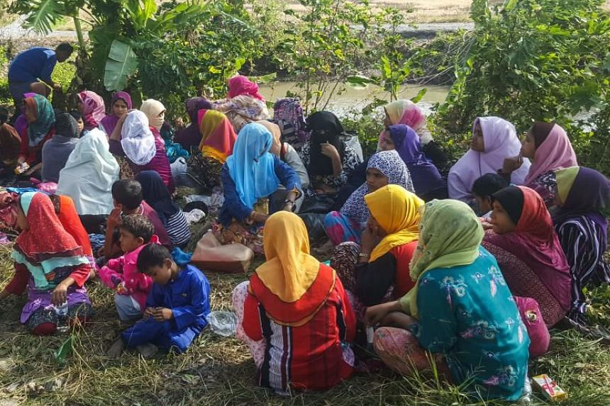Rohingya refugees, who landed on an isolated northern shore near the Malaysia-Thai border, huddle in a group in Kangar on March 1, 2019.