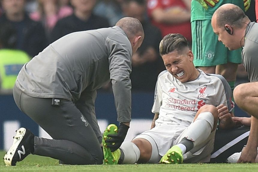 Liverpool's injured Brazilian midfielder Roberto Firmino gets attention on the field.