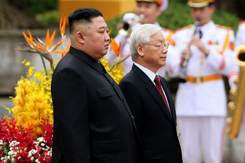 North Korea's leader Kim Jong Un (left) and Vietnam's President Nguyen Phu Trong attend a welcoming ceremony and review an honour guard at the Presidential Palace in Hanoi on March 1, 2019.