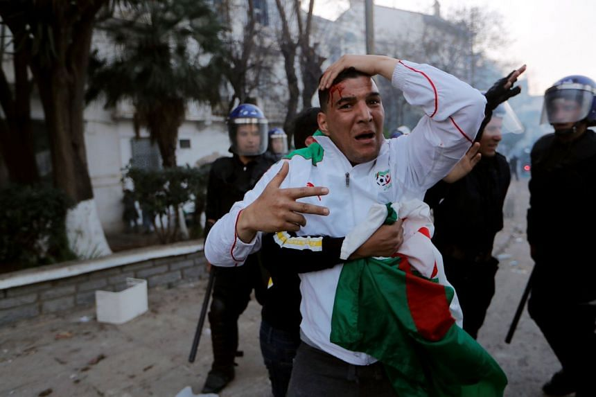 Anti-riot police detain a man who was protesting against President Bouteflika's plan to extend his 20-year rule.