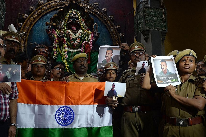 Indian security forces holding up photos of pilot Abhinandan Varthaman during an event to pray for his return in Chennai yesterday.