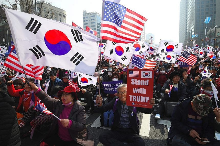 Pro-American protesters waving South Korean and US flags during a rally denouncing the South Korean government's dovish approach and policies on North Korea in Seoul yesterday.