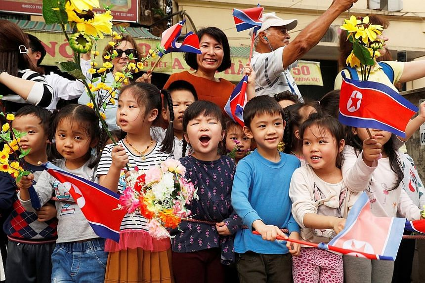 Above: Children cheering as North Korean leader Kim Jong Un's motorcade passed by in Hanoi yesterday. Left: Mr Kim, accompanied by Vietnamese President Nguyen Phu Trong, attending a welcome ceremony at the Presidential Palace in Hanoi yesterday. Mr K