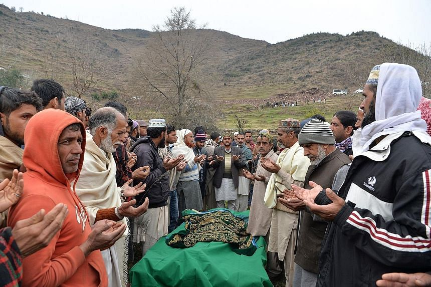 Mourners at the funeral of a woman killed by a blast near the Line of Control. Pakistani soldiers at a checkpoint near the border with India yesterday. The wall of a house that locals say was damaged by firing from the Pakistan side of the border. Pe