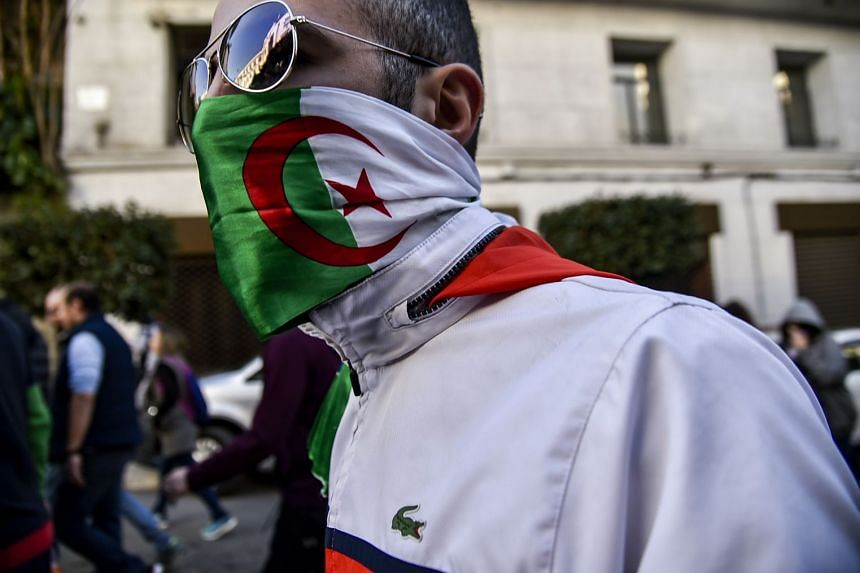 An Algerian protester wearing an Algerian flag as a face-covering marches in the capital Algiers.