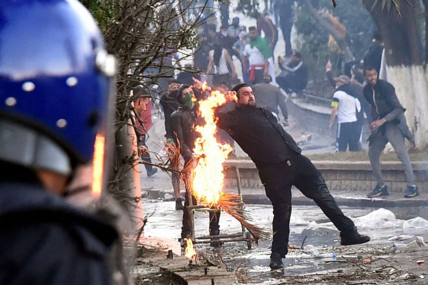 Flames erupt near a man as members of the Algerian security forces respond to protests in the capital Algiers.