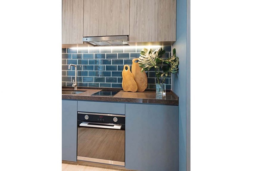 A Prussian blue subway-tiled backsplash in the open-concept kitchen (above) adds a pop of colour.