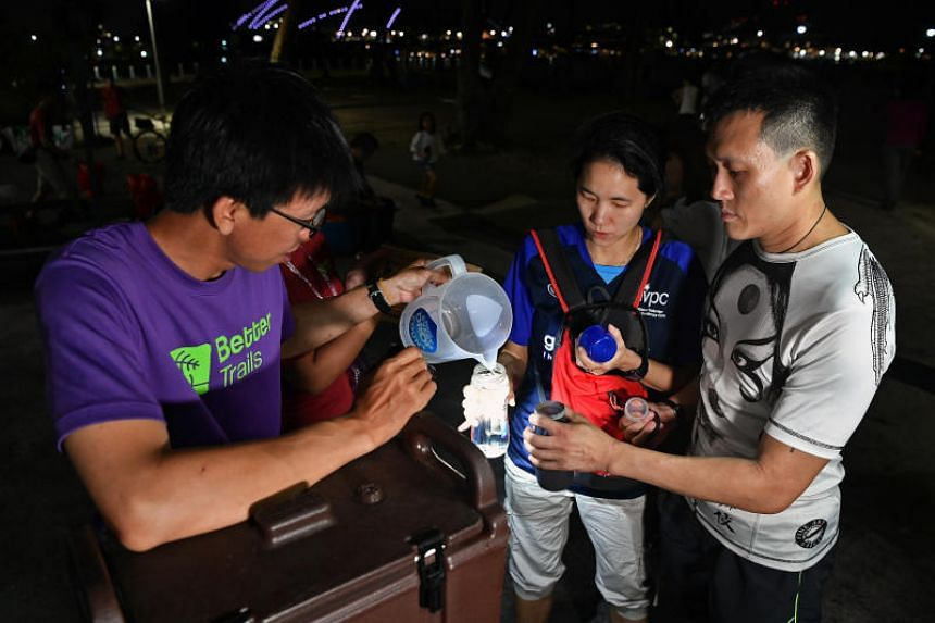 Mr Ding Kian Seng, co-founder of sustainable outdoor recreations company Better Trails, which organised the camp, fills up water bottles for participants Ng Bee Kay and her husband Adam Reutens-Tan.