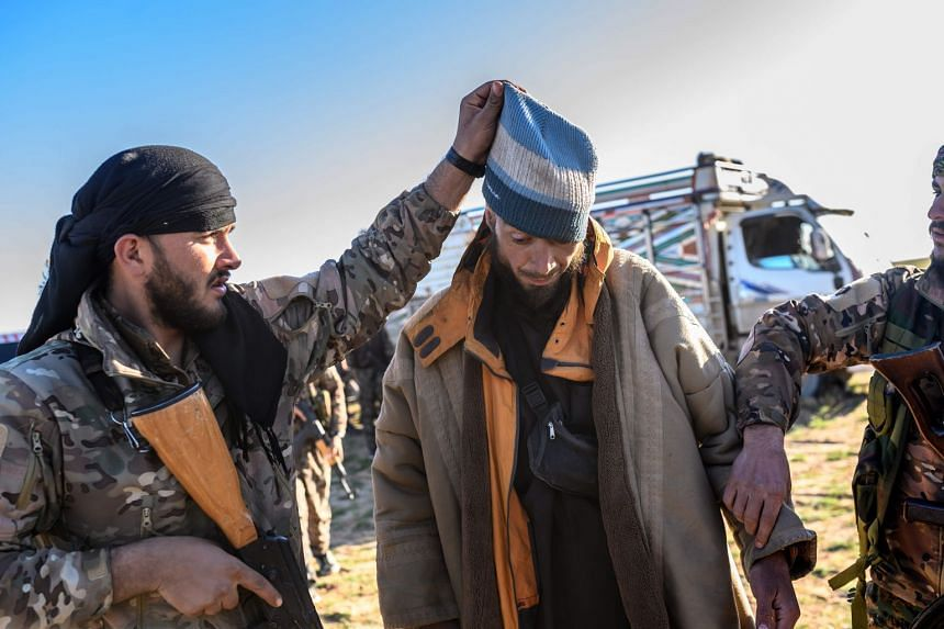 An SDF member raises the hood of a reported Bosnian man who is suspected of being an ISIS militant.