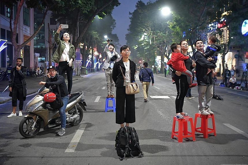 Hanoi residents holding US and North Korean flags as they wait on the street to catch a glimpse of North Korean leader Kim Jong Un departing for the second day of the summit. Mr Kim's bodyguards standing on a vehicle as his motorcade prepares to leav