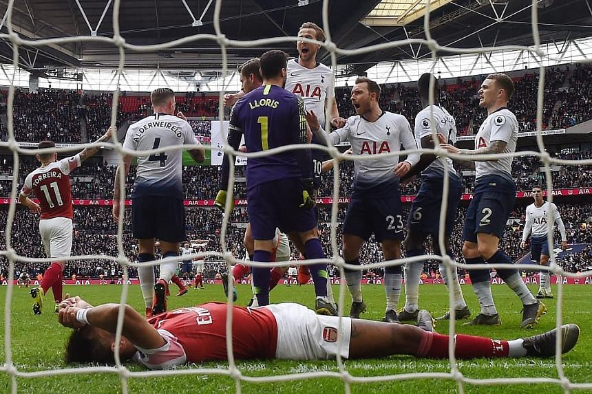 Tottenham Hotspur goalkeeper Hugo Lloris celebrating with teammates after saving a penalty from Arsenal's Pierre-Emerick Aubameyang (front) during their EPL match at Wembley Stadium yesterday which ended 1-1.