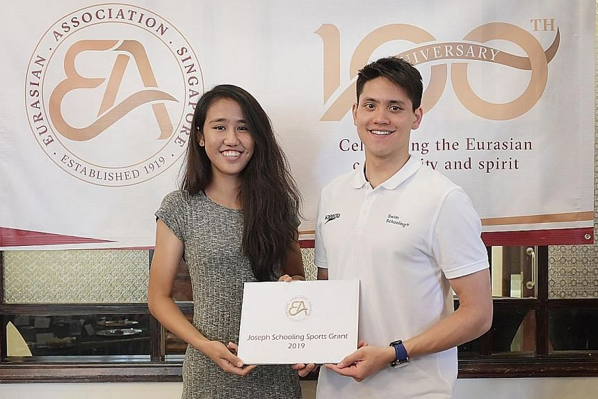 Tia Rozario receiving the Joseph Schooling Sports Grant from Schooling yesterday. The cash grant of $5,000 will go towards Rozario's undergraduate studies and training in the United States.