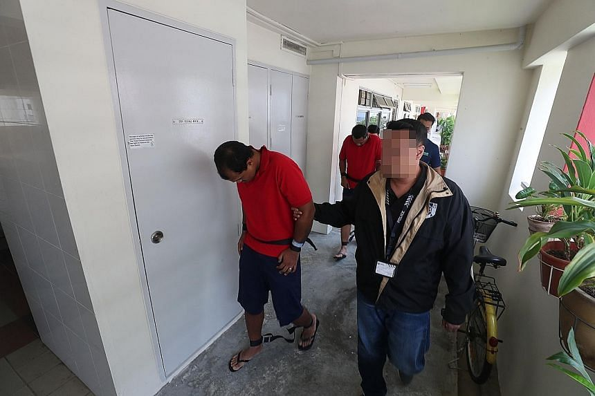 Mohamed Fauzi Abdul Rahman (front) and Mohammad Zahan Saad being taken by police officers on Friday to a Woodlands flat, where they allegedly burned the front door and a pair of slippers outside the apartment.