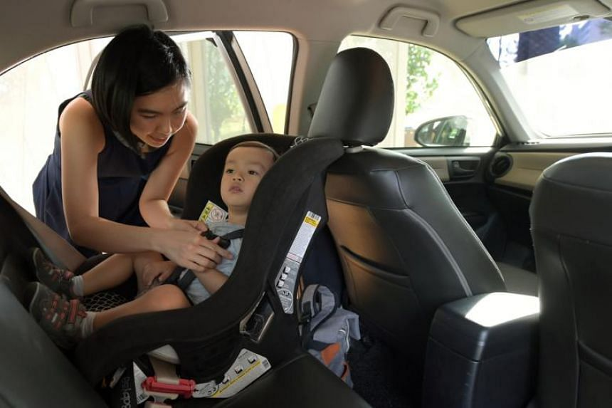 Ms Liu Wen Hsin, 30, putting her child, Spence Lowe, 2, into a car seat at the back of their car.