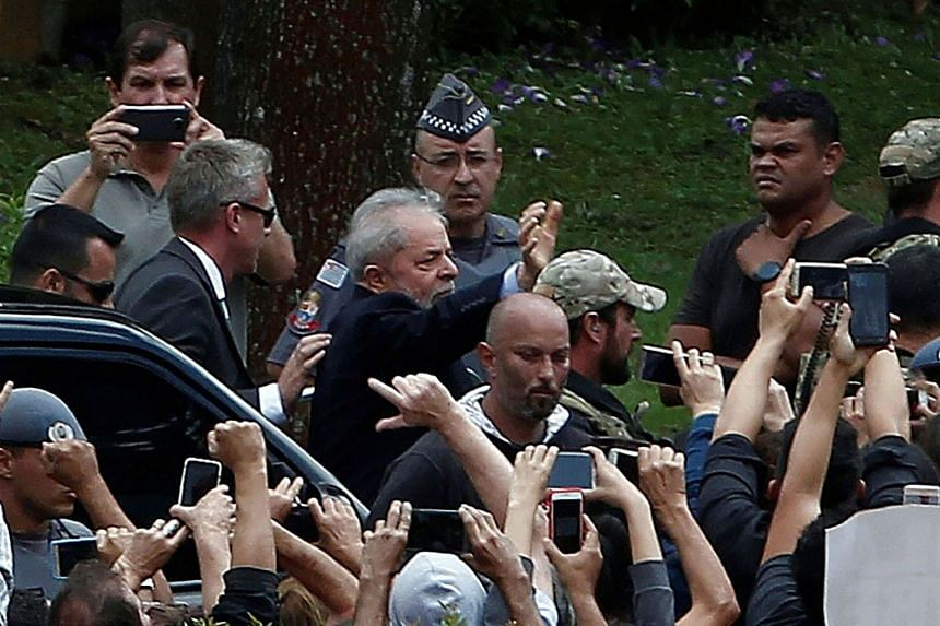 Lula (centre, waving) is escorted by security forces upon arrival at Jardim da Colina cemetery.