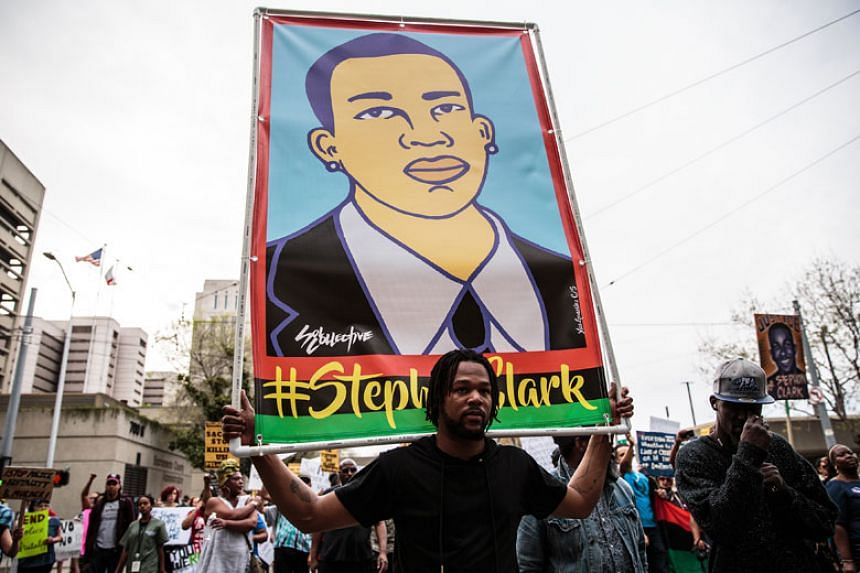A protester carries an image of Stephon Clark during a march in Sacramento, on April 4, 2018.