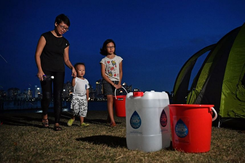 Ms Adeline Goh, her son Ging Wai, four, and daughter Yan Wan, 10, outside their tent at the water conservation camp.