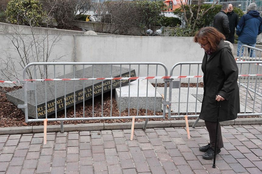 A woman walks by the memorial stone marking the site of Strasbourg's Old Synagogue.