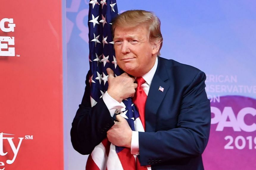 Trump hugs the US flag as he arrives to speak at the annual Conservative Political Action Conference.