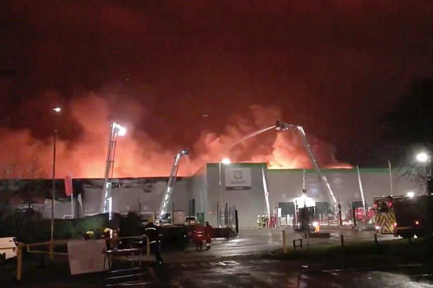 Firefighters putting out a blaze at Ocado's flagship robotic distribution centre in Andover, Britain, on Feb 5, 2019.