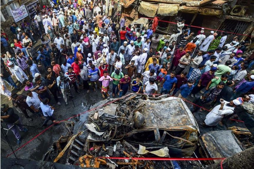 Residents gathering around the wreckage of cars that were destroyed in a fire in Dhaka, on Feb 22, 2019.