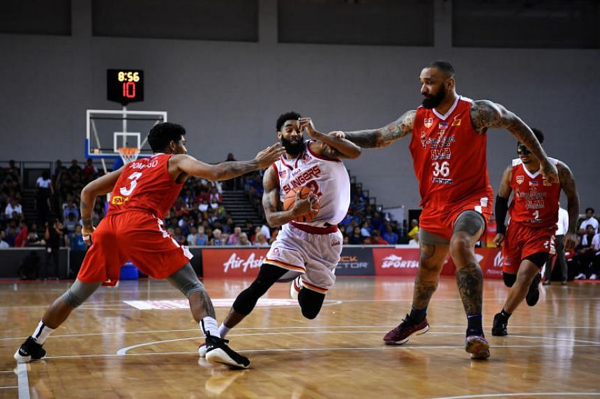 Singapore Slingers guard Jerran Young (centre) driving against Alab Pilipinas forwards Lawrence Domingo (#3) and Peter John Ramos (#36) during their Asean Basketball League match on March 3, 2019.