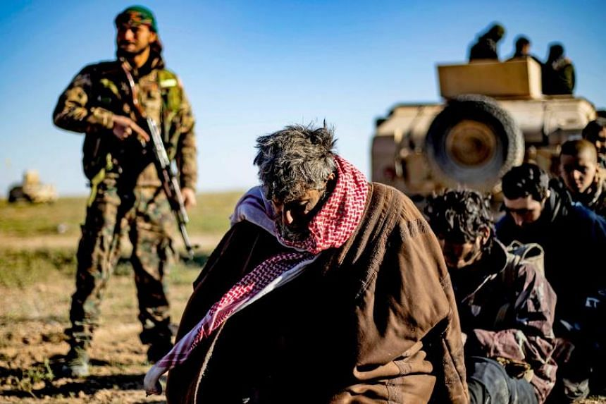 Men and boys suspected of being ISIS fighters waiting to be searched by members of the Syrian Democratic Forces, near Baghouz, Syria, on March 1, 2019.