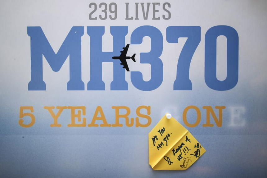 A message written on a paper plane is seen on a display during a remembrance ceremony marking the fifth anniversary of the disappearance of flight MH370, in KL on March 3, 2019.