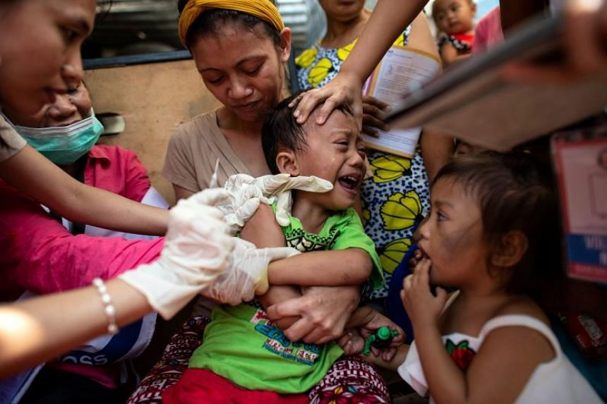 A child receiving a measles vaccine from a Philippine Red Cross worker, in the Baseco slum area of Manila on Feb 16, 2019.