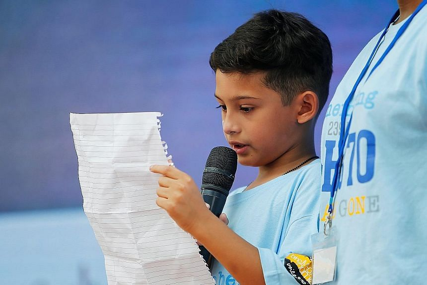 """A girl with """"MH370"""" painted on her cheek was among those at yesterday's ceremony. A recovered wing flap (left) and messages from families of the missing (below left) were on display. Rafael Gomes (below, right), grandson of missing in-flight supervis"""