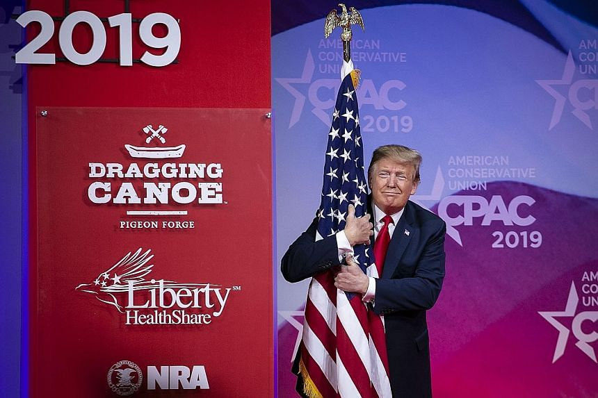 """President Donald Trump hugging an American flag before speaking at the Conservative Political Action Conference in Maryland last Saturday. He spoke about the """"socialist"""" ideas touted by the Democrats and vowed that America will never be a socialist c"""