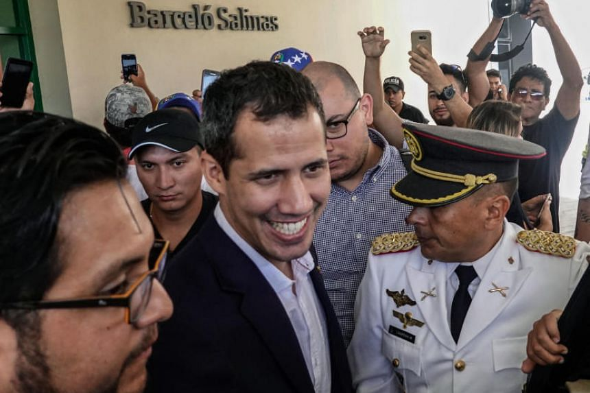 Venezuelan opposition leader and self-proclaimed acting president Juan Guaido (centre) is surrounded by supporters and journalists as he leaves his hotel in Salinas, Ecuador on March 3, 2019.
