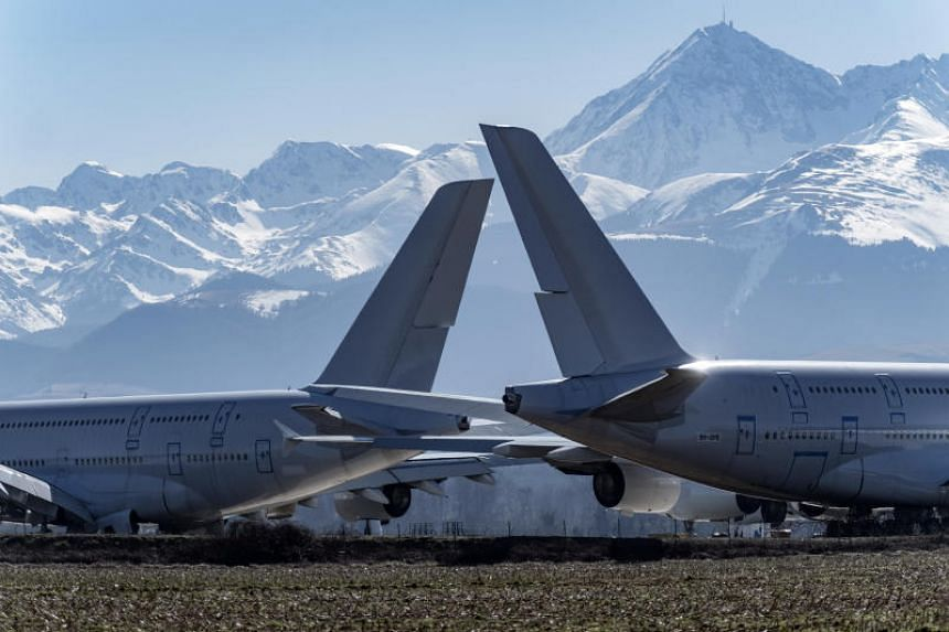 Two Airbus A-380 aircraft sit on the ground at the Tarmac Aerosave SAS storage and recycling facility against a background of the Pyrenees mountain range in Tarbes, France, on Feb 17, 2019.