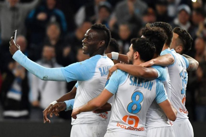 Marseille's Italian forward Mario Balotelli (left) takes a selfie with teammates after scoring during the French L1 football match between Olympique de Marseille and AS Saint-Etienne at the Velodrome Stadium in Marseille, southern France on March 3,