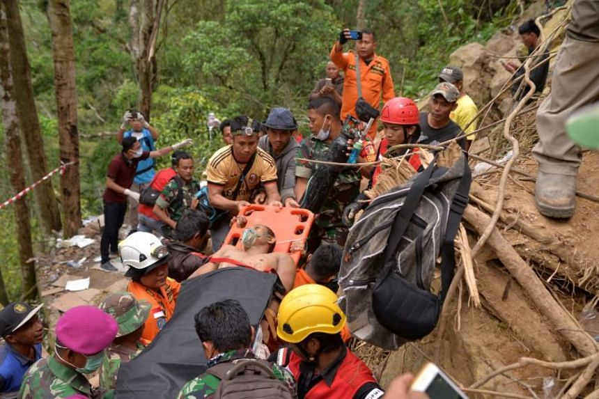 Members of an Indonesian search and rescue team carry a survivor of a mine collapse in Bolaang Mongondow, north Sulawesi, on Feb 28, 2019.