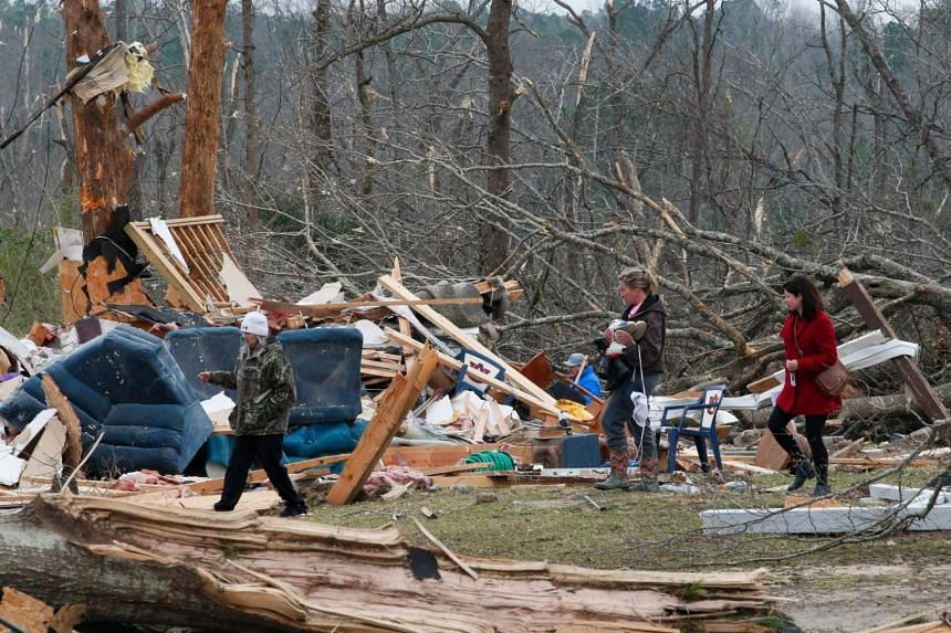 Residents look for belongings on March 4, 2019, at a home after it was destroyed in a tornado in Beauregard, Alabama.