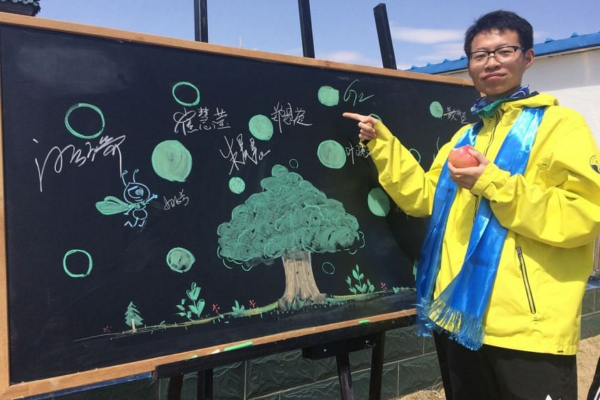 Mr Geng Geng next to a commemorative board at Ant Forest's nursery in Inner Mongolia during a trip organised by the company last year. He has ''planted'' 10 trees to date, including several in Inner Mongolia.