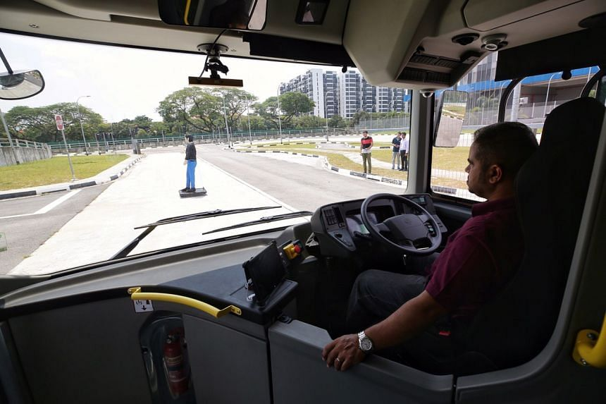 """The NTU-LTA-Volvo Autonomous Bus coming to a halt within sight of an errant """"pedestrian"""" (represented by a moving dummy) during a trial at Cetran on March 4, 2019."""