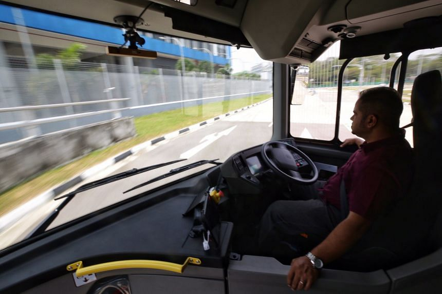 A driver manning (but with his hands off the steering wheel) the NTU-LTA-Volvo Autonomous Bus as it turns at a tight corner during a trial at Cetran.