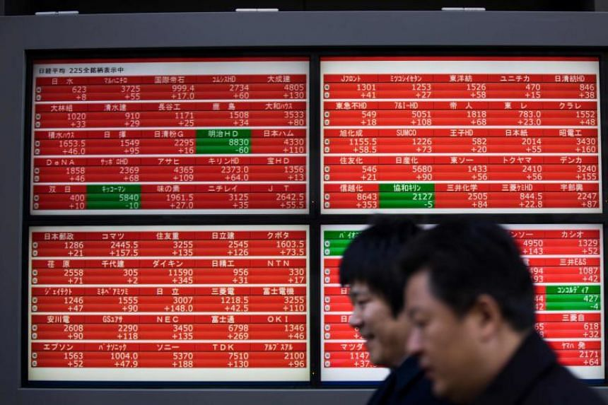 Pedestrians walk past a stock indicator board displaying share prices of the Tokyo Stock Exchange in Tokyo on January 7, 2019.