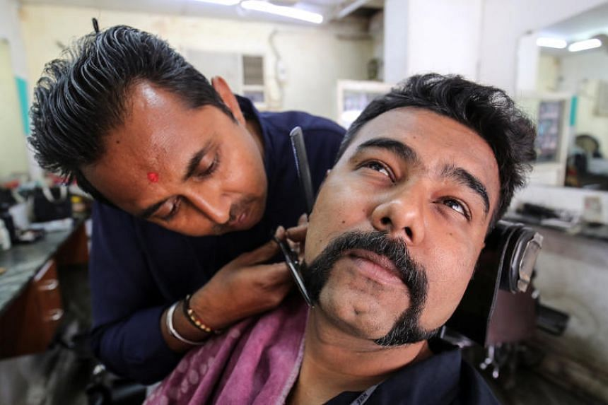 Mr Dhiren Makvana gets his moustache trimmed in a similar style to the one sported by Indian Air Force pilot Abhinandan Varthaman, who was captured and later released by Pakistan, inside a salon in Ahmedabad, India, on March 4, 2019.