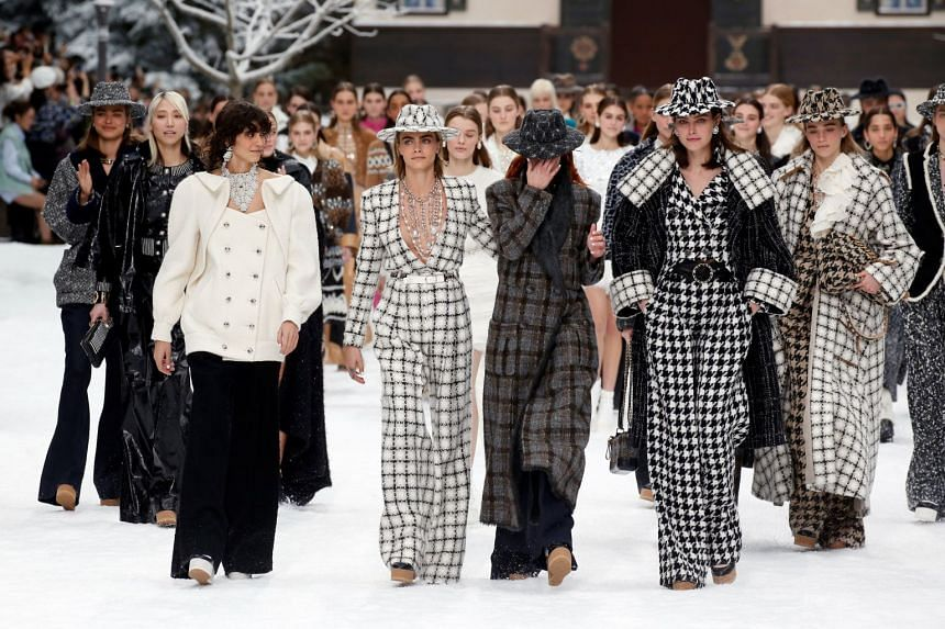 Cara Delevingne and other models react while presenting creations by late designer Karl Lagerfeld.