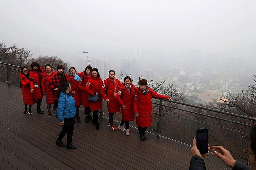 Chinese tourists posing for a photo with the view of central Seoul shrouded by fine dust in the background yesterday.