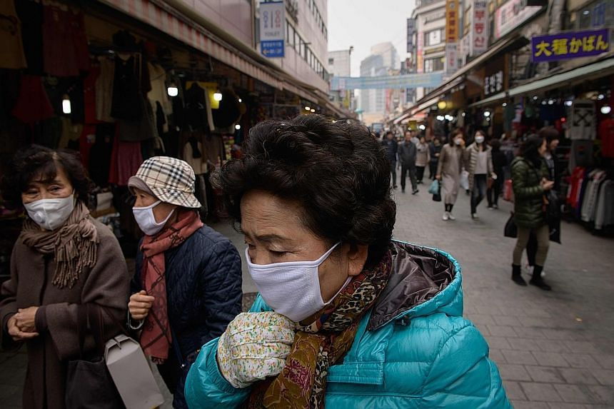 Shoppers wearing face masks as heavy air pollution hit Seoul yesterday. President Moon Jae-in has ordered the government to take extraordinary measures to fight fine dust pollution.