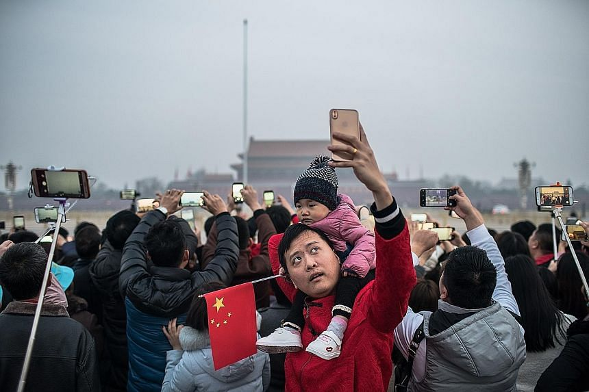 Delegates and journalists attending the National People's Congress held at the Great Hall of the People in Beijing yesterday. People taking photos while waiting for the flag-raising ceremony at Tiananmen Square before the NPC's opening yesterday.
