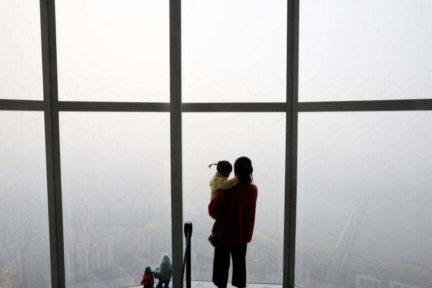 A woman holding her baby in her arms looks at a view of Seoul shrouded by fine dust during a polluted day in Seoul, South Korea, March 6, 2019.