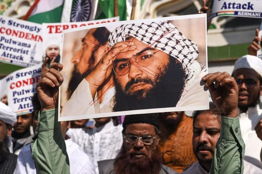 Indian Muslims hold a scratched photo of Jamaat-ud-Dawa organisation chief, Hafiz Saeed, as they shout slogans against Pakistan during a protest in Mumbai on Feb 15, 2019.