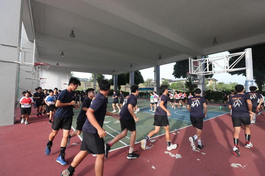 The basketball team of Christ Church Secondary School having physical training at the basketball court. Co-curricular activity need not mean intense competition for everyone, says the writer.