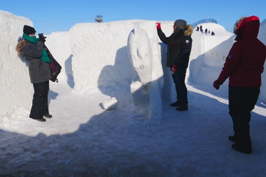 People take pictures near a statue carved out of snow and located within the snow maze in St Adolphe, Canada, on March 2, 2019.